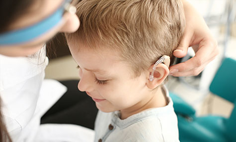 Image of young boy being fitted with hearing aid