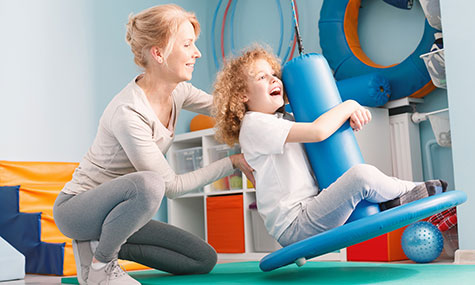 Image of woman assisting young girl with physical movement.