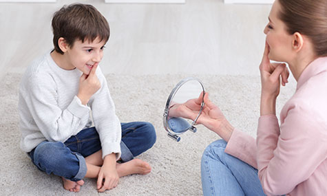 Image of woman teaching young boy with speech therapy