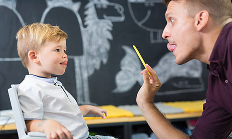 Image of male teach working on speech therapy with young boy