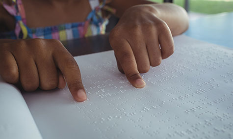 Close up image of young girl's hands reading Braille